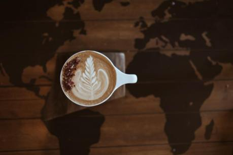 A latte sits atop a table painted with a map of the world. Photo by Alina Mendoza.